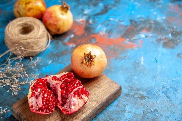Ansicht von unten köstliche granatäpfel auf schneidebrett strohfaden auf blauem abstraktem hintergrund