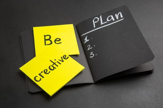 Ansicht von unten kreativ sein, geschrieben auf haftnotizen, die auf schwarzem notizblock auf schwarzem hintergrund geschrieben sind