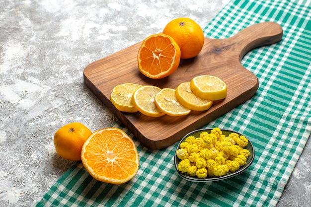 Ansicht von unten orangen zitronenscheiben auf holzbrett gelbe bonbons in schüssel auf grün-weiß kariertem tisch