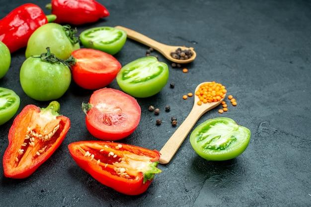 Ansicht von unten rote und grüne tomaten geschnitten paprika schwarzer pfeffer gemütliche rote linsen in holzlöffeln auf dunklem tisch