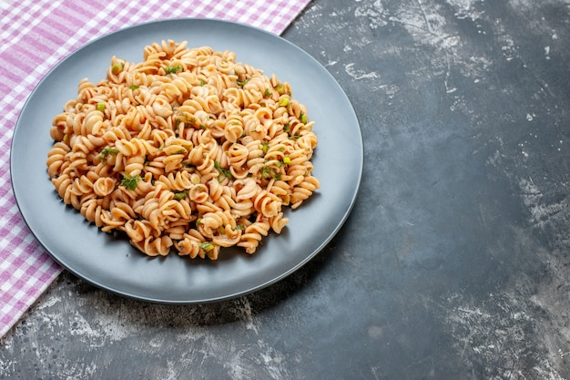 Ansicht von unten rotini pasta auf rundem teller auf rosa weiß karierter tischdecke auf dunkler oberfläche mit freiem platz free