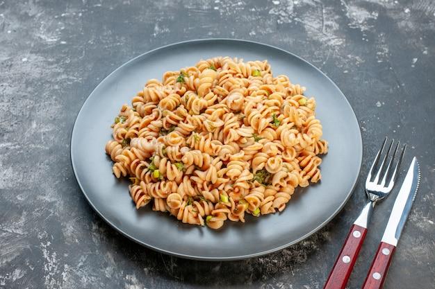 Ansicht von unten rotini pasta auf runder teller gabel und messer auf dunklem tisch