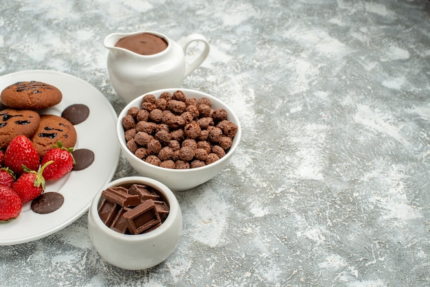 Ansicht von unten schokoladenkekse erdbeeren und runde pralinen auf dem weißen ovalen teller und schalen mit pralinen müsli und kakao auf der linken seite des grauweißen bodens