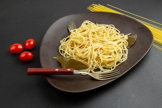Ansicht von unten spaghetti nudeln mit lorbeerblätter gabel auf teller kirschtomaten rohe spaghetti nudeln auf schwarzem hintergrund