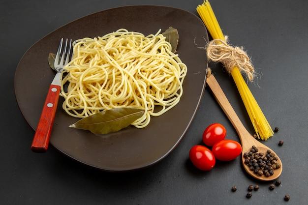 Ansicht von unten spaghetti nudeln mit lorbeerblättern auf teller gabel holzlöffel kirschtomaten auf dunklem hintergrund