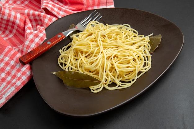 Ansicht von unten spaghetti-nudeln mit lorbeerblattgabel auf tellertischdecke auf schwarzem hintergrund