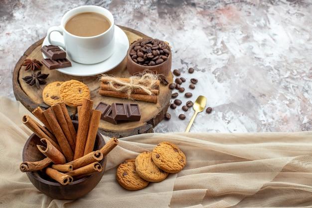 Ansicht von unten tasse kaffeekekse schüssel mit kaffeebohnen schokoladen-zimt-sticks in schüssel anis sterne auf holzbrett auf tisch mit freiem platz