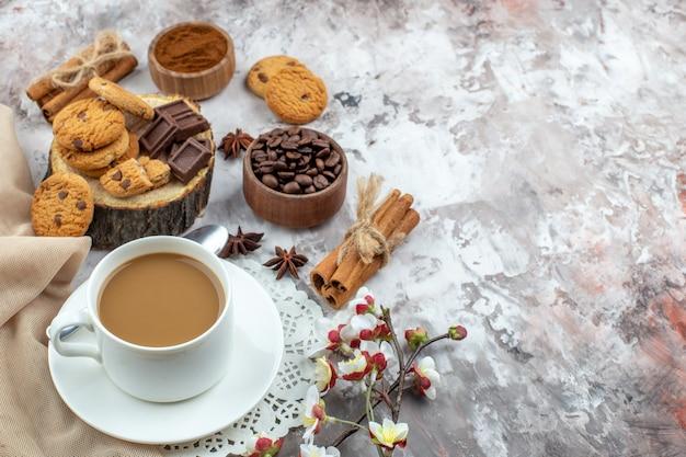 Ansicht von unten tasse kaffeeschale mit gerösteten kaffeebohnen schokoladen-zimt-sticks kekse auf tisch frei platz