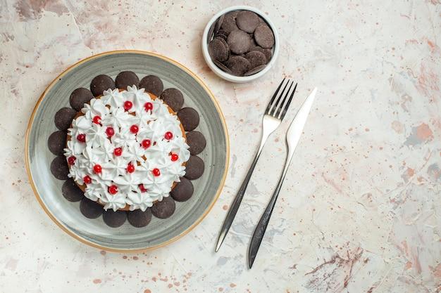 Ansicht von unten torte mit gebäckcreme auf ovalem teller schokolade in schüsselgabel und tafelmesser auf beigem tisch