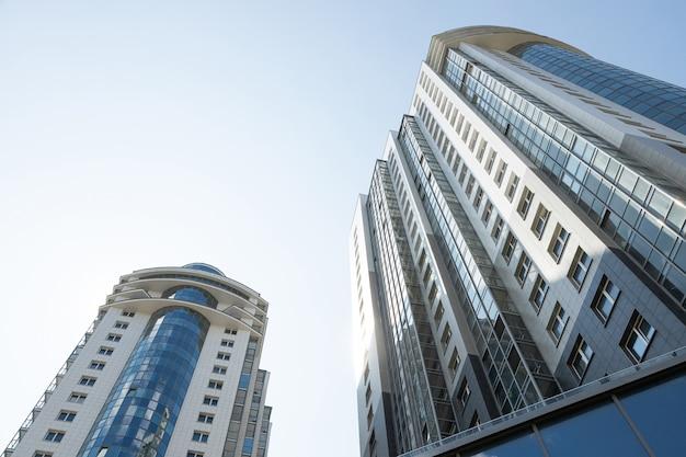 Ansicht von unten von zwei hohen wohngebäuden am hintergrund des blauen himmels