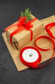 Ansicht von unten weihnachtsgeschenk in braunem papier zweig tannenband auf zeitung auf dunklem hintergrund kopie raum
