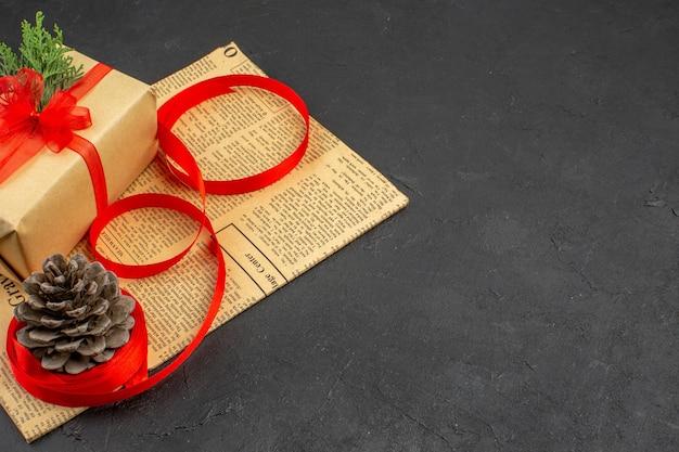 Ansicht von unten weihnachtsgeschenk in braunem papier zweig tannenband auf zeitungs-tannenzapfen auf dunklem hintergrund