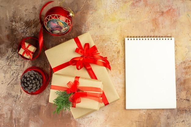 Ansicht von unten weihnachtsgeschenke in braunem papierband weihnachtsbaum spielzeug auf zeitung im dunkeln