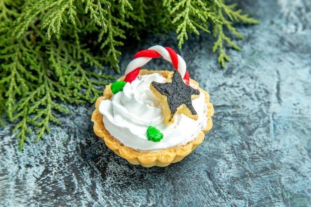 Ansicht von unten weihnachtstörtchen tannenzweig auf grauem tisch
