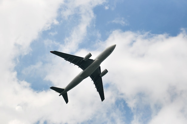 Ansicht von unterhalb des verkehrsflugzeugflugzeuges, das am bewölkten himmel des sonnigen tages fliegt