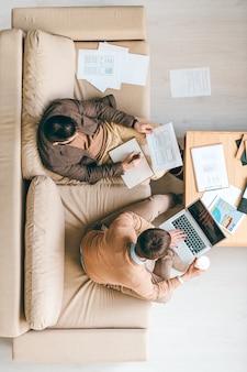 Ansicht von zwei jungen kreativen software-designern, die über neue website-oberfläche oder anwendung durch arbeitsplatz arbeiten