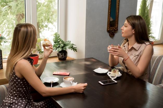 Ansicht von zwei jungen schönen frauen, die einander am restauranttisch während des mittagessens gegenüber sitzen