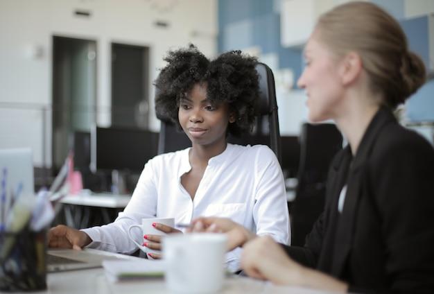 Ansicht von zwei weiblichen mitarbeitern, die nebeneinander in einem bürokonzept sitzen: rivalität, mitarbeiter