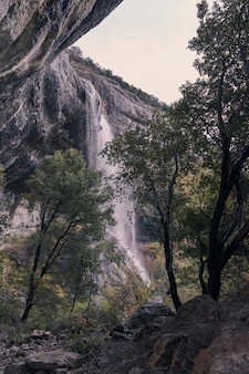Ansichten eines wasserfalls zwischen felsen und bäumen an einem typischen grauen spätherbsttag.