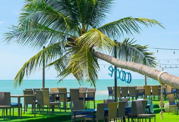 Ansichten von kokosnussbäumen und von speisetischen des strandes bei songkhla, thailand.