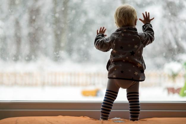 Ansichtsform hinter dem kleinkindkind, das vor einem großen fenster steht, das sich dagegen lehnt und draußen auf eine schneebedeckte natur schaut.