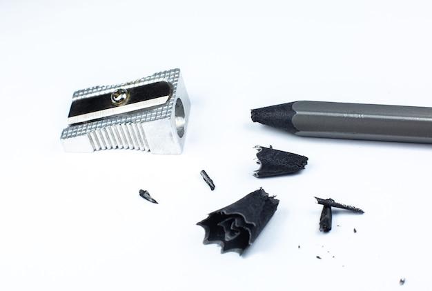 Anspitzer und ein gebrochener bleistift. späne und ein graphit auf weißem hintergrund. nahaufnahmefoto.