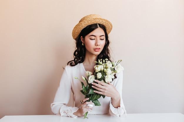 Ansprechende asiatische frau, die weiße blumen hält. studioaufnahme des glückseligen chinesischen modells mit eustoma-blumenstrauß.
