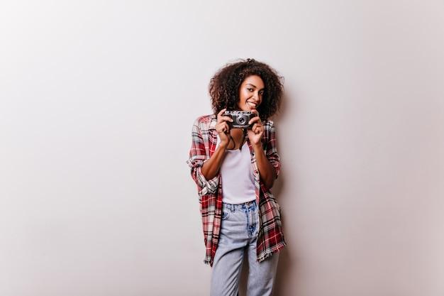Ansprechende braunhaarige frau mit stehender kamera. lächelnde afrikanische weibliche shotgrapher lokalisiert auf weiß.