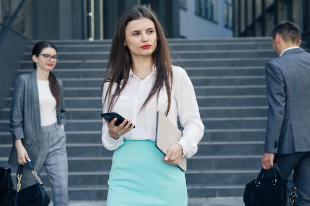 Ansprechende büroleiterin für junge frauen mit smartphone eingabe von social media-nachrichten im geschäftsviertel. erfolg. geschäftsleute. technologie.