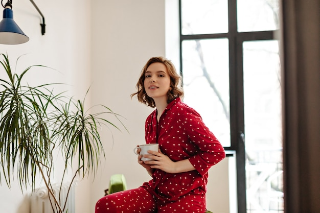 Ansprechende europäische frau im pyjama, die tasse kaffee hält und kamera betrachtet. innenaufnahme der jungen frau, die am morgen zu hause aufwirft.