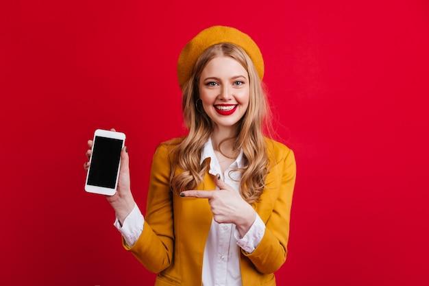 Ansprechende französische frau, die smartphone mit leerem bildschirm hält. vorderansicht des mädchens in der gelben baskenmütze, die mit finger auf digitales gerät zeigt.