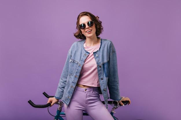 Ansprechende frau in jeansjacke, die mit fahrrad aufwirft. innenaufnahme der selbstbewussten lockigen dame isoliert.