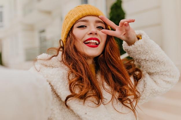 Ansprechende frau mit ingwerhaar, das im kalten wintertag aufwirft. außenfoto des schönen rothaarigen mädchens.