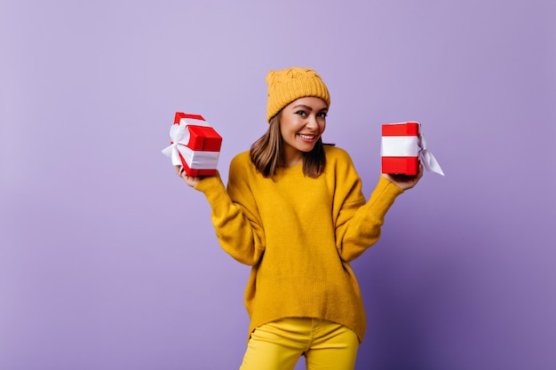 Ansprechende junge frau im lässigen gelben hut lächelnd. gut gekleidetes stilvolles mädchen, das mit geburtstagsgeschenken aufwirft.