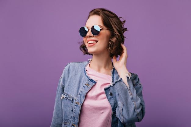 Ansprechende junge frau in funkelnder sonnenbrille, die in der ferne schaut. porträt des glamourösen europäischen modells mit dem kurzen haarschnitt lächelnd.
