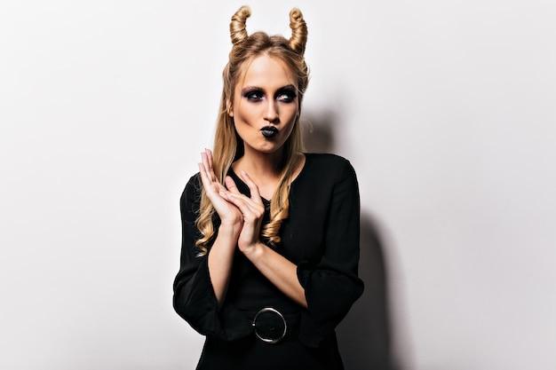 Ansprechende kaukasische frau in der vampirkleidung, die im karneval aufwirft. hübscher zauberer im schwarzen kleid, der halloween genießt.