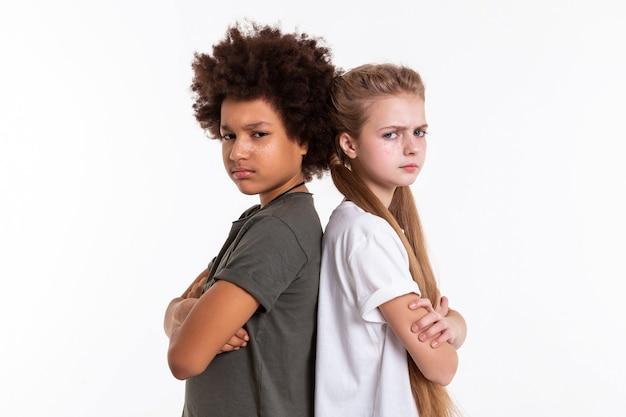 Ansprechende kinder. wütende verärgerte kinder, die mit gekreuzten händen rücken an rücken stehen und extrem entschlossen aussehen