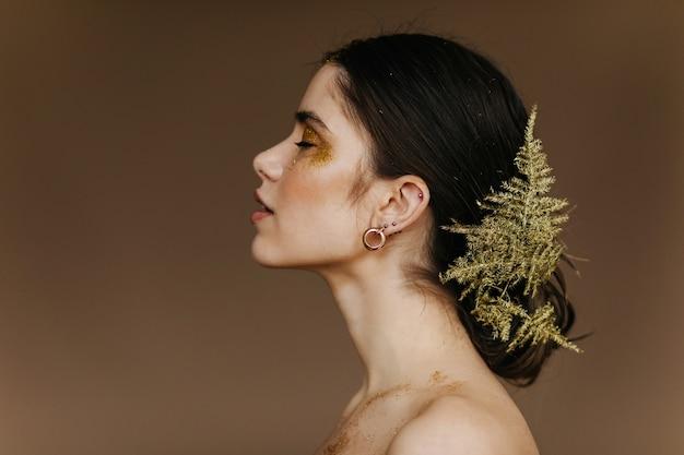 Ansprechendes kaukasisches mädchen mit der pflanze in der haaraufstellung. nahaufnahmeporträt der niedlichen europäischen frau mit goldenen ohrringen.
