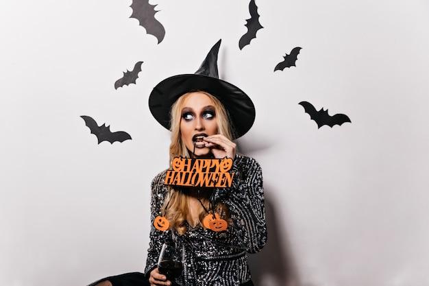 Ansprechendes kaukasisches mädchen mit dunklem make-up, das im zaubererkostüm am karneval aufwirft. innenfoto der blonden gewinnenden dame, die an halloween kühlt.
