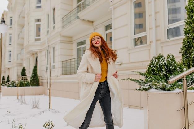 Ansprechendes mädchen im weißen kittel, das auf der straße tanzt. attraktives europäisches weibliches modell, das mit lächeln im winter aufwirft.