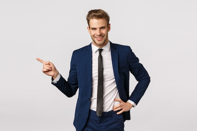 Anspruchsvoller charismatischer blonder geschäftsmann mit borste, klassischer anzug der abnutzung, nach links zeigend und lächeln und erklären über großes produkt, annoncieren finanz-app, geschäftskonzept