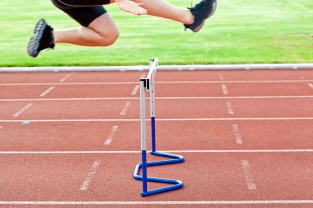 Anspruchsvoller männlicher athlet, der über hecke während eines rennens springt