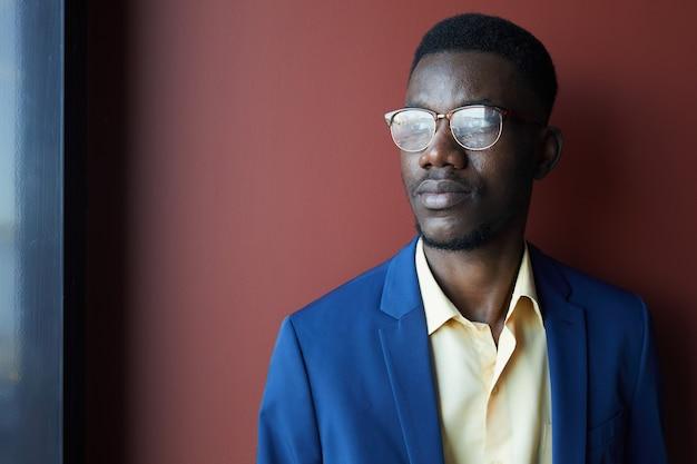 Anspruchsvolles porträt des eleganten afroamerikanischen mannes, der brille trägt und weg schaut, während er gegen kastanienbraunen hintergrund, kopierraum aufwirft