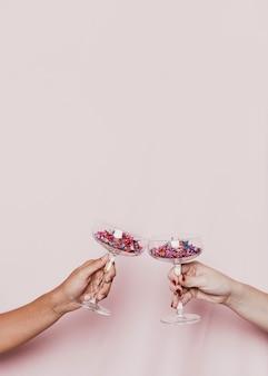 Anstoßen mit konfetti gefüllten gläsern