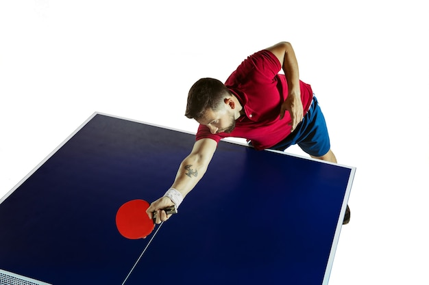 Anstrengend. junger mann spielt tischtennis auf weißer wand. modell spielt tischtennis. konzept der freizeitaktivität, sport, menschliche emotionen im gameplay, gesunder lebensstil, bewegung, aktion, bewegung.