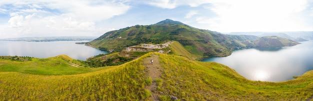 Antenne: blick auf den tobasee und die insel samosir von oben auf sumatra indonesien. riesige vulkanische caldera mit wasser bedeckt, traditionelle batak-dörfer, grüne reisfelder, äquatorialwald.