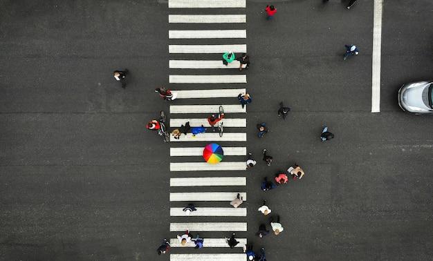 Antenne. menschen drängen sich auf fußgängerüberweg. zebrastreifen, draufsicht. eine person aus der menge hält einen bunten regenschirm.