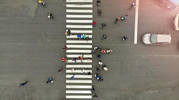 Antenne. menschen drängen sich auf fußgängerüberweg. zebrastreifen, draufsicht.
