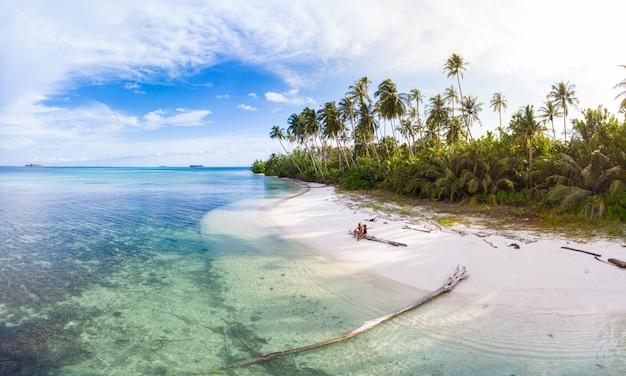Antenne: paar entspannt am tropischen strand bei sonnenuntergang, weg von allem, karibischen meer weißen sandstrand. banyak-inseln sumatra indonesien