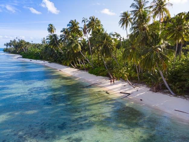 Antenne: paar entspannt am tropischen strand bei sonnenuntergang, weg von allem, karibischen meer weißen sandstrand.